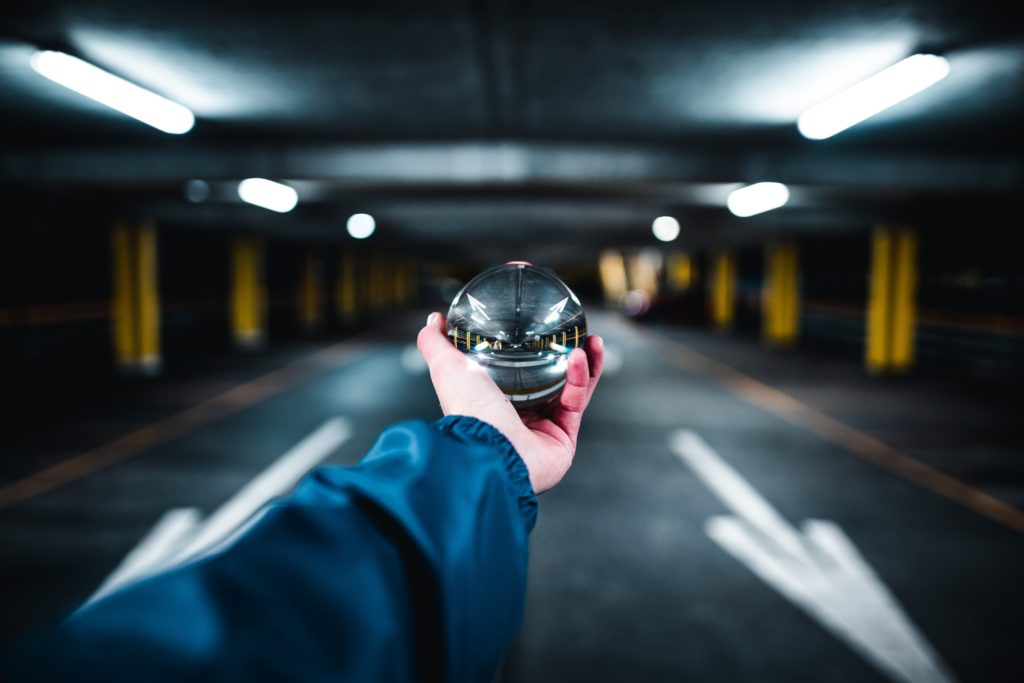 hand holding clear ball that brings into focus the blurred background