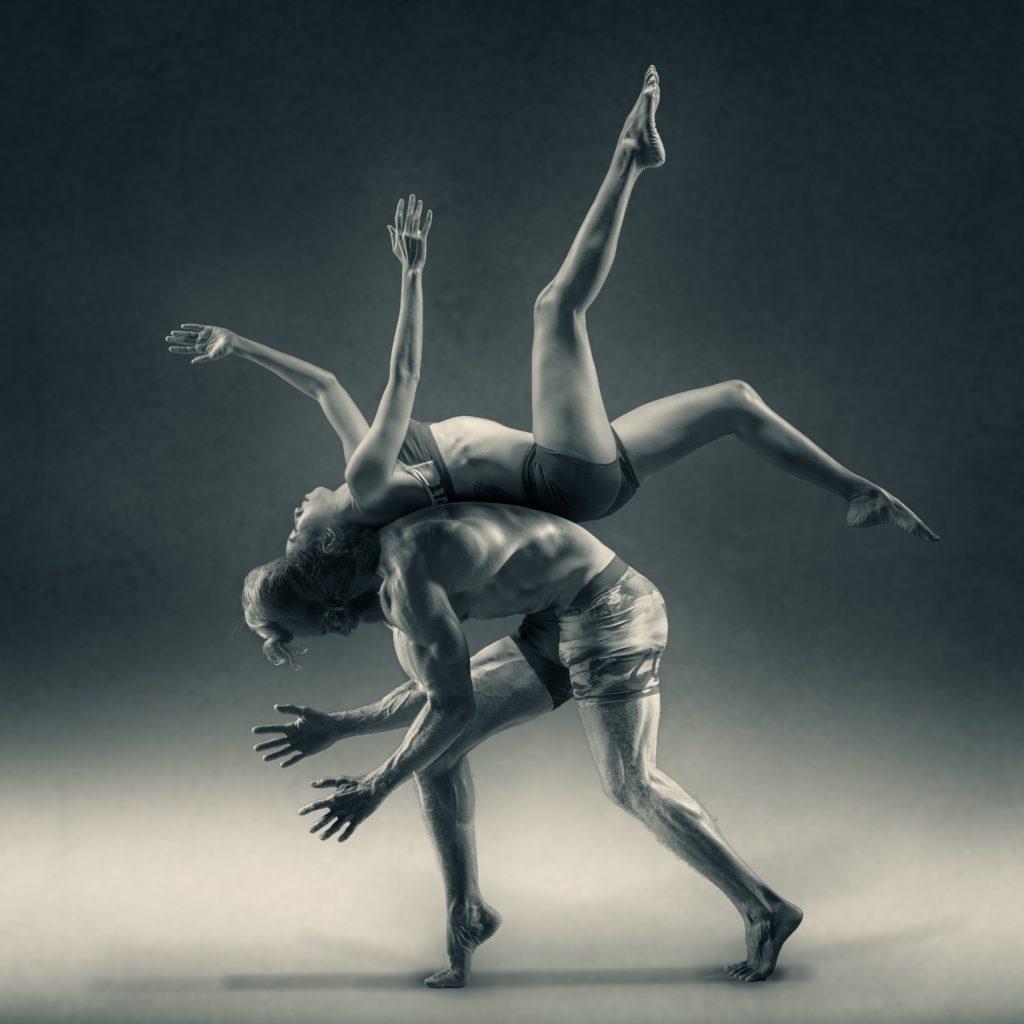 Man balancing women on his back. Both showing flexibility